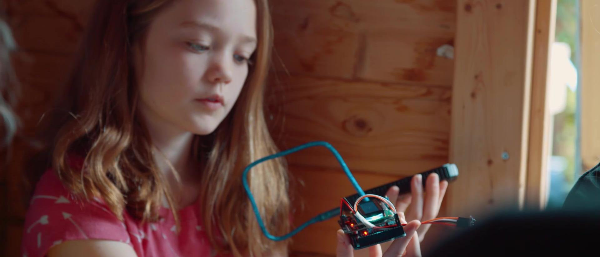 Young girl looking at a homemade electronic device.