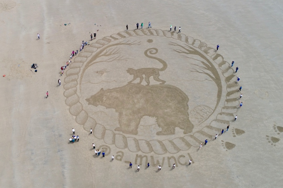 Sand art showing a bear and monkey on Cefn Sidan beach